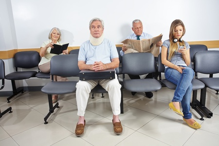 Different people sitting in a waiting room of a hospital photo