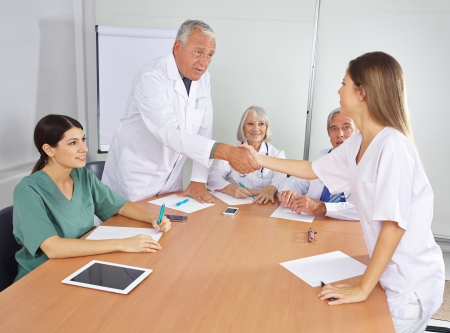 physician: Doctor greeting new colleague in team with handshake Stock Photo