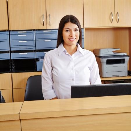 recepcionista: Sonriente mujer workingt feliz en la recepción en un hospital