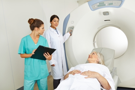 tomography: Radiologist and nurse with senior patient in MRI in a hospital Stock Photo