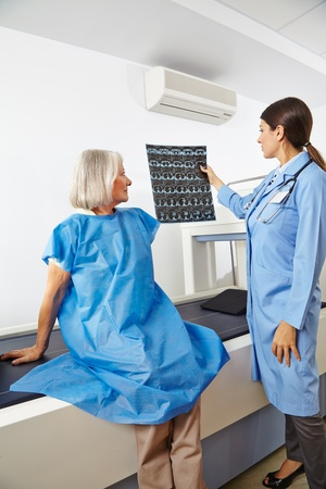instrument of measurement: Doctor looking at x-ray images of a senior patient in radiology Stock Photo