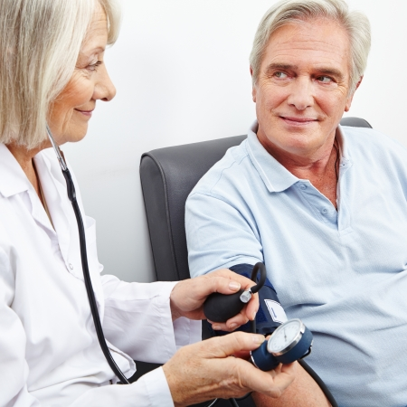 hypotension: Senior patient at blood pressure measurement smiling at doctor