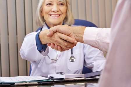 medical notes: Smiling doctor and patient giving handshake after a consultation