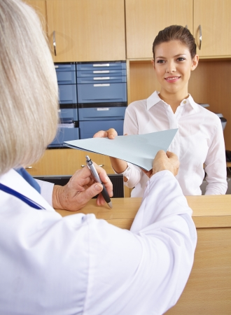 Doctor getting medical records in hospital from the\ receptionist
