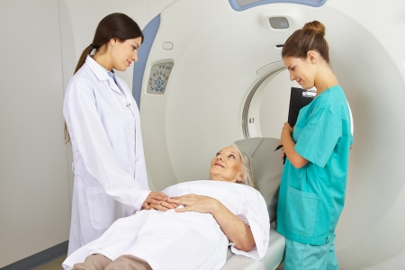 Doctor and MTA talking with patient on MRI machine in radiology in a hospital photo
