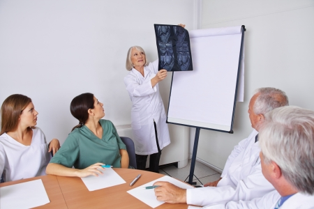 Doctor at a team meeting with other physicians looking at a x-ray image photo