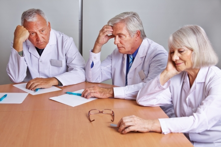 Three worried doctors thinking in a team meeting