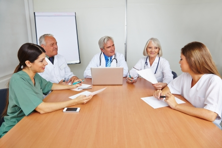 Group of doctors with applicant at job interview for a hospital photo