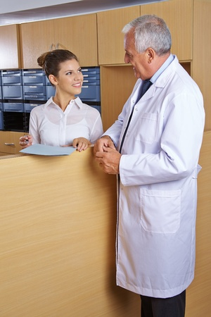 Doctor talking to female receptionist in a hospital photo