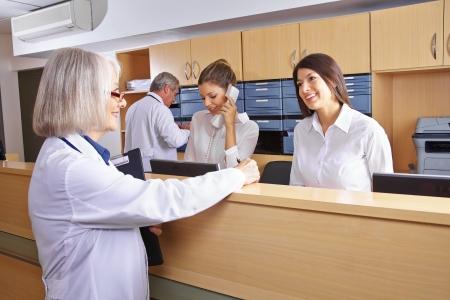 Senior arts praten met receptioniste bij receptie ziekenhuis