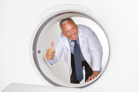 resonancia magnetica: Feliz médico sosteniendo su pulgar hacia arriba en el tubo de la máquina de resonancia magnética en un hospital