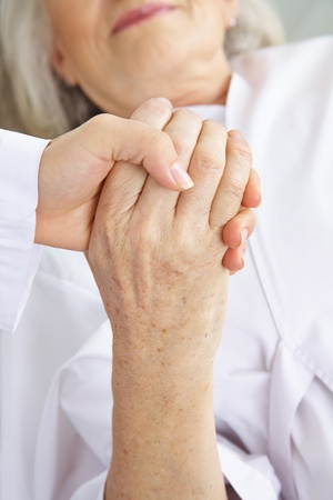 eldercare: Doctor holding hand of senior woman patient for comfort in a hospital