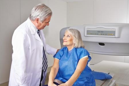 osteoporosis: Doctor que habla con paciente mayor antes de la medición de la densidad ósea en radiología