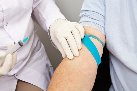 provision: Doctor with syringe at blood withdrawal looking for a blood vessel Stock Photo