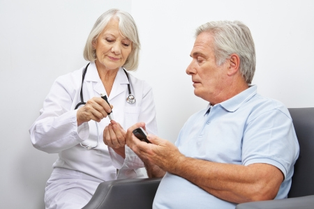 Doctore making blood sugar test for senior man in her office photo