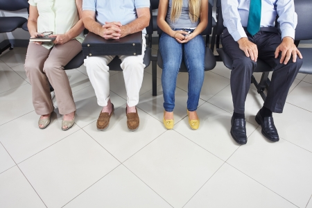 Feet of different people sitting in a waiting room Stock Photo - 21380375