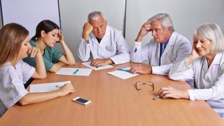 grupo de doctores: Pensativo equipo de m�dicos y enfermeras en una reuni�n