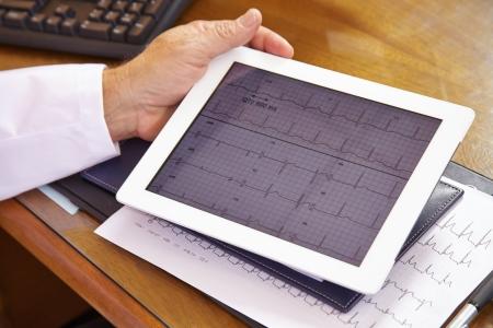 electrocardiograma: Cuide la mirada de ECG en un equipo Tablet PC en su oficina Foto de archivo