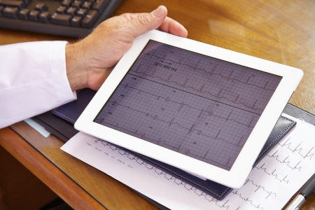 cardiologist: Doctor looking at ECG on a tablet computer in his office