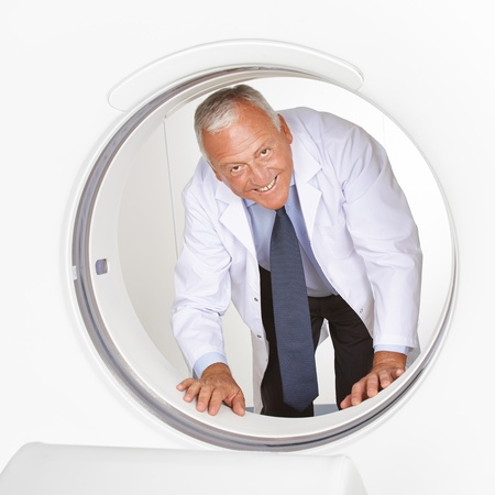 Happy senior doctor looking through tube of MRI scanner in radiology photo
