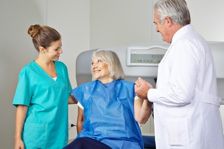 osteoporosis: Doctor y MTA ayuda a la mujer mayor en radiolog�a en la medici�n de la densidad �sea Foto de archivo