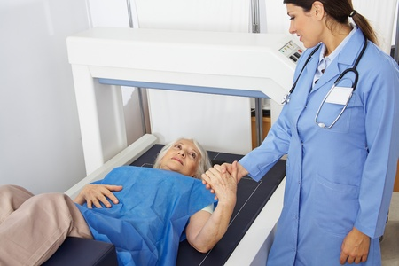 internal medicine: Senior woman holding hand of doctor in radiology while getting bone density measurement