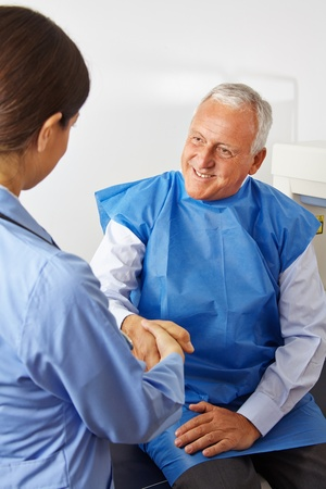 internal medicine: Senior patient in radiology shaking hand of doctor in a hospital
