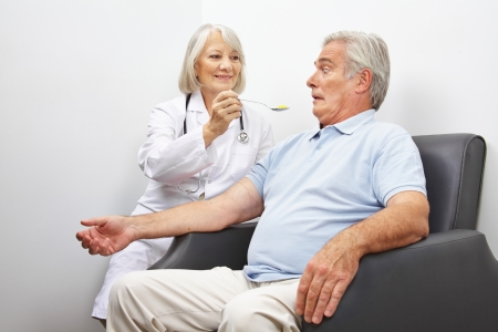 mimic: Doctor feeding shocked patient with a spoonful of pills Stock Photo