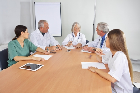 staff meeting: Doctor making work schedule in team meeting with colleagues Stock Photo