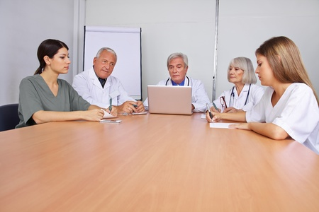 Many doctors sitting in a team meeting on a round table photo