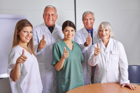 Successful doctor and MTA team holding their thumbs up photo