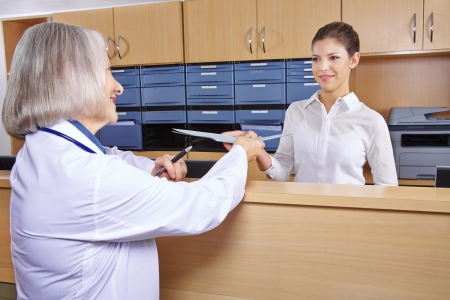 medical records: Senior doctor at hospital reception getting medical records