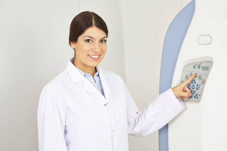 Doktor naciskając przycisk z jej palcem w maszyny MRI w radiologii Zdjęcie Seryjne