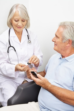 Senior man with diabetes getting blood sugar measurement from doctor Stock Photo