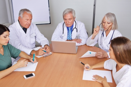 Team of many doctors talking in a group meeting photo