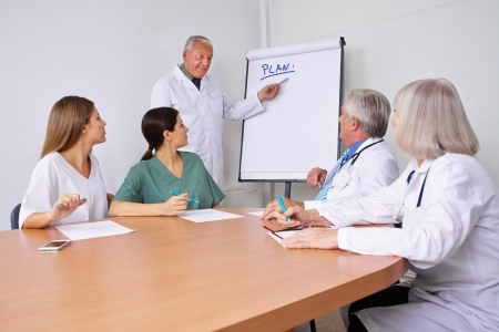Doctor in a team presentation explaining his plan on a flipchart photo