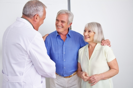 Doctor greeting happy senior couple with a handshake in a hospital photo