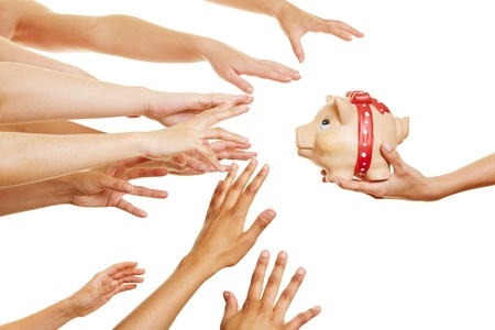 Many hands reaching for money in a piggy bank in a hand photo