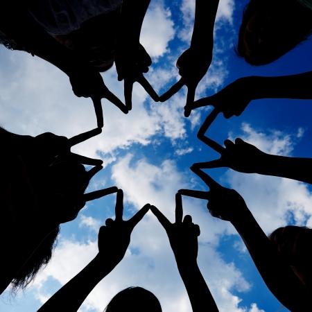 apoyo familiar: Silueta de muchas manos formando red en estrella bajo un cielo