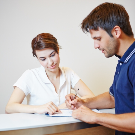 healthcare office: Man filling out patient form at doctors office with the help of a doctors assistant