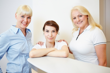 Female dentist standing with doctors assistant and receptionist at the reception photo