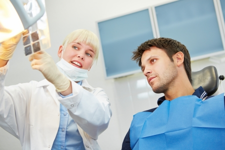 Female dentist showing patient caries on x-ray image prior to dental treatment photo
