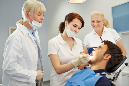 approbation: Dental assistant taking approbation test with two dentists