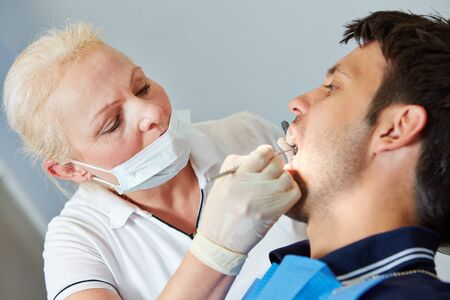 Senior dentist looking for caries in mouth of patient photo
