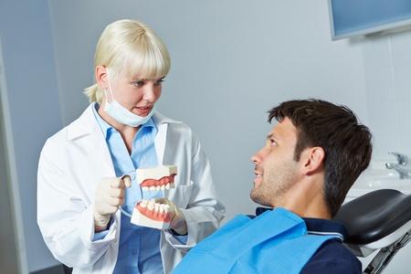 denture: Dentist showing denture to patient prior to examination