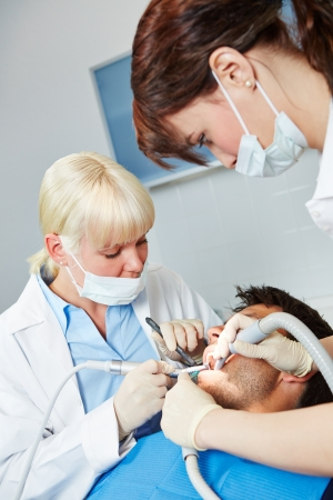 Dentist operates in patient with toothache with dental assistant photo