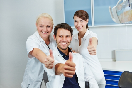 Happy dentist and smiling dental team holding their thumbs up in dental practice photo