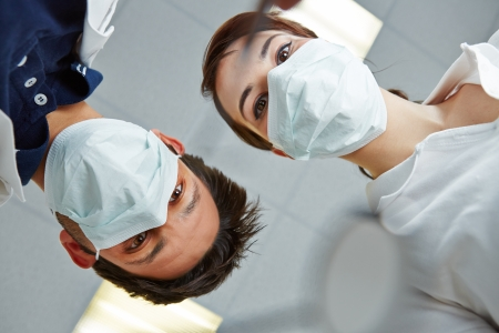 Dentist and dental assistant looking from above in patient POV photo