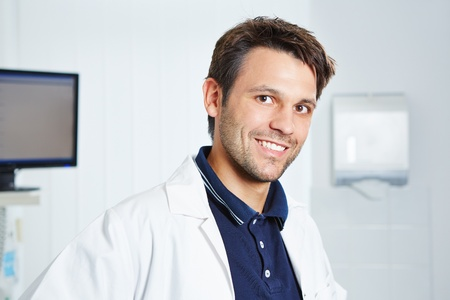 Portrait of a happy dentist in a white lab coat in dental practice photo