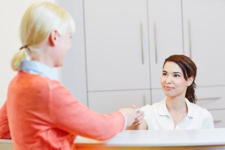 checking in: Patient at doctor reception checking in for dentist appointment Stock Photo